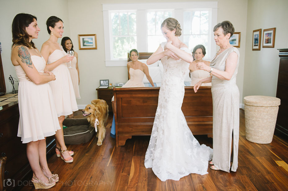 Mother and bridesmaids helping bride into dress