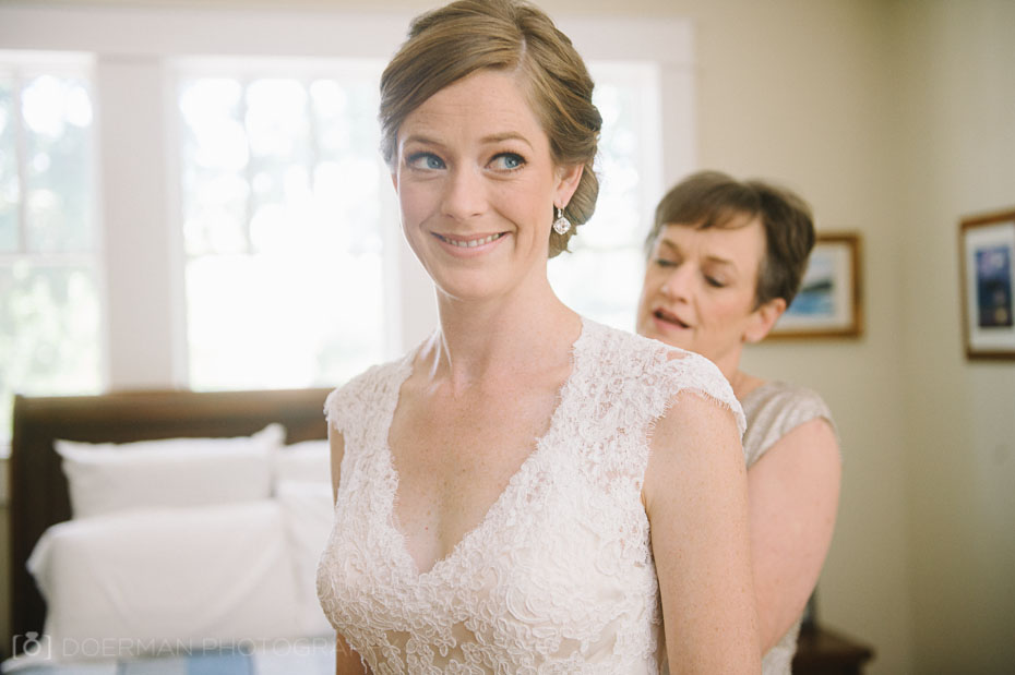 Bride with mom putting on her lacy wedding dress